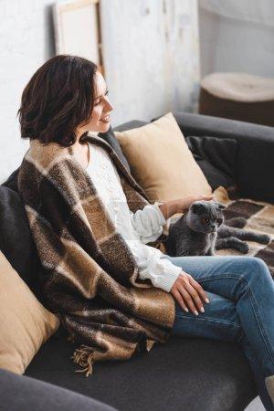 Photo pour Jolie femme dans la couverture assis sur le canapé avec chat - image libre de droit