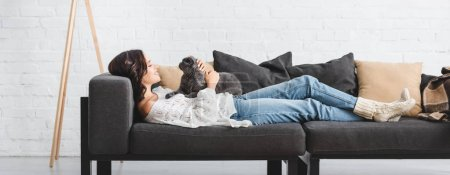 Photo for Attractive woman lying on sofa with scottish fold cat in cozy living room - Royalty Free Image