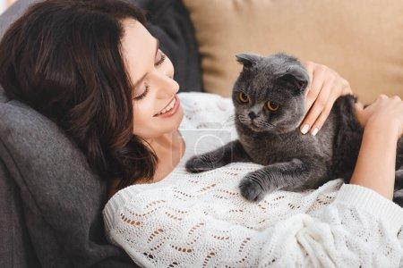 Photo pour Belle femme allongée sur un canapé avec chat plié scottish - image libre de droit