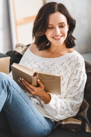 beautiful cheerful girl reading book on sofa at home