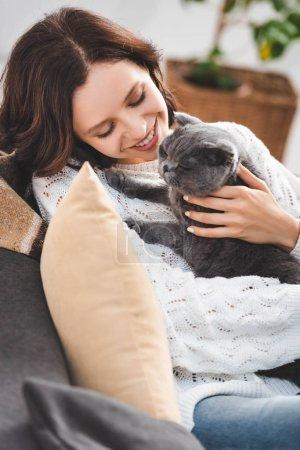 Photo pour Belle jeune femme assise sur canapé avec chat pliant écossais - image libre de droit