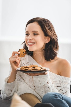 Photo for Beautiful happy woman eating cookies at home - Royalty Free Image