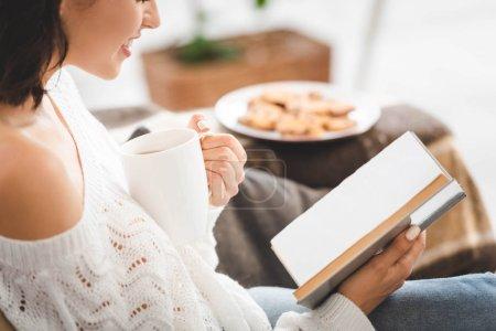 Photo pour Vue recadrée du livre de lecture fille sur canapé avec tasse de café et biscuits - image libre de droit