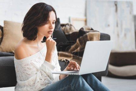 Photo pour Attrayante fille étudiant en ligne avec écouteurs et ordinateur portable - image libre de droit