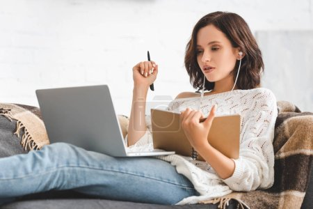 Photo for Attractive girl studying online with notepad, earphones and laptop - Royalty Free Image