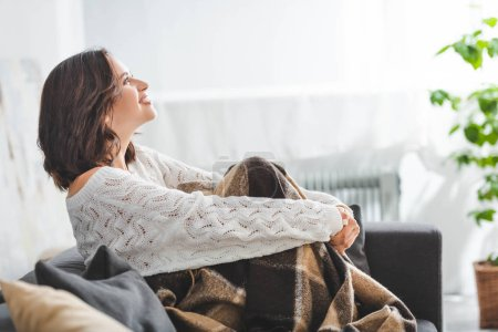 Photo for Happy brunette girl in blanket sitting on sofa in cozy living room - Royalty Free Image