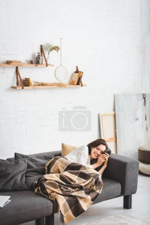 Photo pour Happy woman with closed eyes relaxing in blanket in cozy living room - image libre de droit