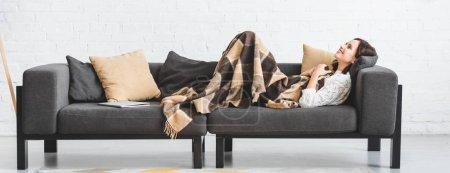 Photo pour Jolie brune en couverture allongée sur un canapé avec un ordinateur portable - image libre de droit