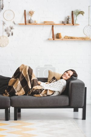 Photo for Beautiful smiling girl in blanket lying on sofa in cozy living room - Royalty Free Image