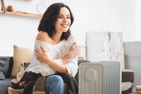 Photo pour Belle femme gaie dans la chambre froide avec chauffage - image libre de droit