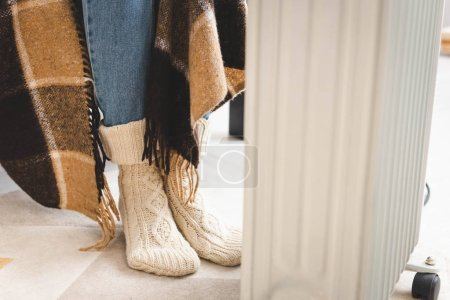 Photo for Girl in knitted socks warming up with blanket and heater - Royalty Free Image