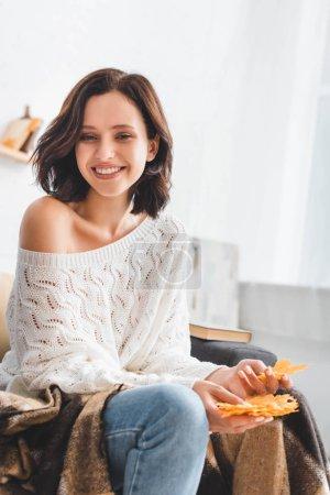 Photo pour Belle fille brune heureuse tenant jaune feuilles d'automne à la maison - image libre de droit