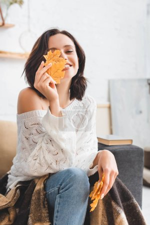 Photo pour Jolie fille heureuse tenant jaune feuilles d'automne devant le visage - image libre de droit