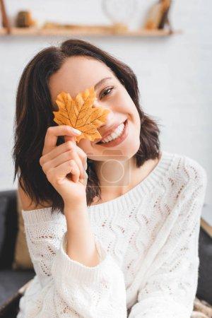 Photo pour Belle fille heureuse tenant jaune feuille d'automne devant le visage - image libre de droit