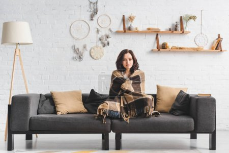 Photo pour Attractive cold girl warming up with blanket on sofa in living room with dream catchers - image libre de droit