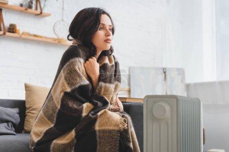 Photo pour Attrayant fille échauffement avec couverture et chauffage dans la chambre froide - image libre de droit