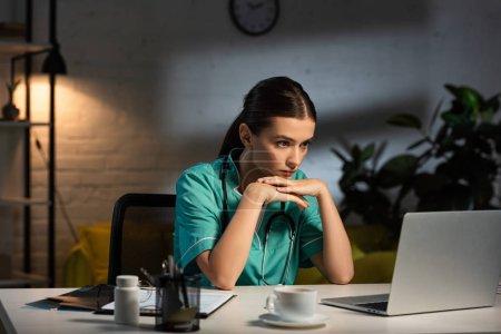 attraktive Krankenschwester in Uniform, die während der Nachtschicht am Tisch sitzt und auf den Laptop schaut