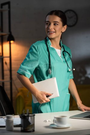 Photo pour Infirmière attrayante en uniforme souriant et tenant un carnet pendant le quart de nuit - image libre de droit