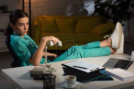 attraktive Krankenschwester in Uniform sitzt am Tisch und hält Hörer während der Nachtschicht