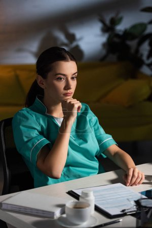 attractive and pensive nurse in uniform sitting at table during night shift