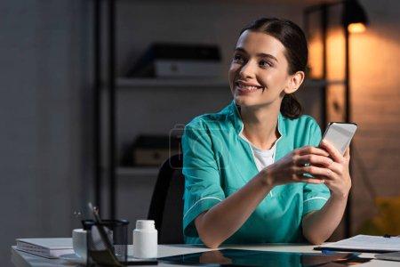 Lächelnde Krankenschwester in Uniform sitzt am Tisch und nutzt während der Nachtschicht das Smartphone