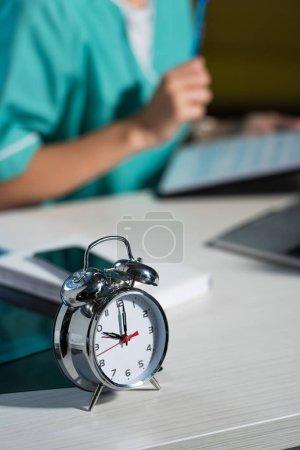 Photo pour Mise au point sélective de la montre d'alarme sur la table en bois pendant le quart de nuit - image libre de droit