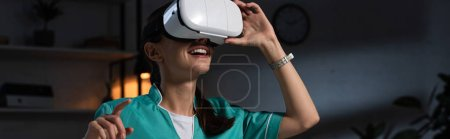 Photo for Panoramic shot of nurse in uniform with virtual reality headset pointing with finger during night shift - Royalty Free Image