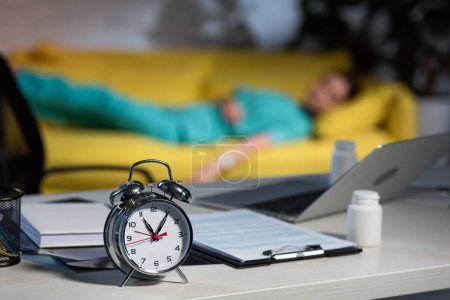 Photo pour Selective focus of alarm watch, clipboard and notebook on table - image libre de droit