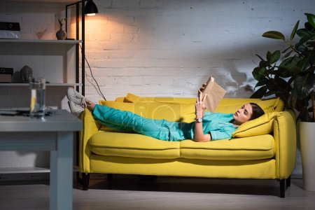 Photo for Attractive nurse in uniform lying on sofa and reading book during night shift - Royalty Free Image