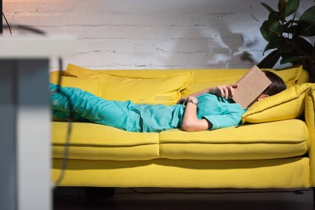 Photo for Selective focus of nurse in uniform lying on sofa with book on face during night shift - Royalty Free Image