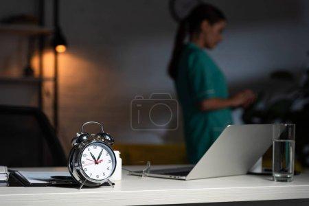 Photo pour Selective focus of alarm watch, glass and laptop - image libre de droit