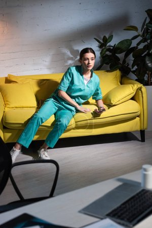 Photo for Nurse in uniform sitting on sofa and looking away during night shift - Royalty Free Image