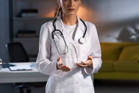 Photo pour Cropped view of doctor in white coat with stethoscope during night shift - image libre de droit