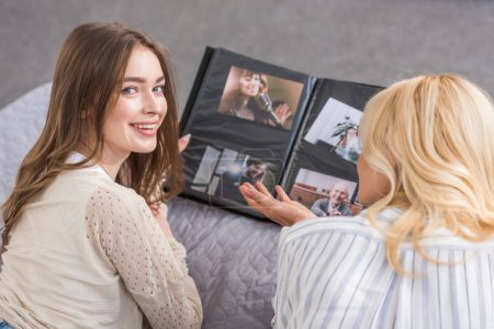 Photo pour Joyeuse fille regardant la caméra tout en étant couché sur le lit près de la mère regardant l'album photo - image libre de droit