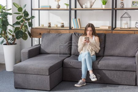 Photo for Pretty girl using smartphone while sitting on sofa in living room - Royalty Free Image