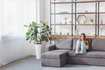 Photo pour Pretty girl using smartphone while sitting on sofa in living room - image libre de droit