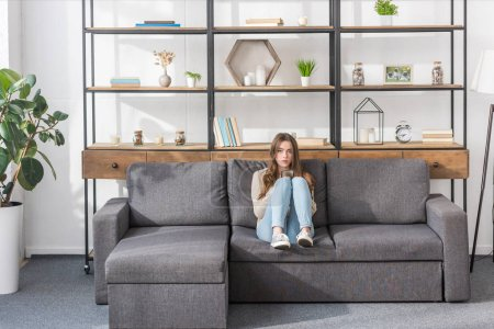 Photo for Pretty girl looking at camera while sitting on sofa at home - Royalty Free Image
