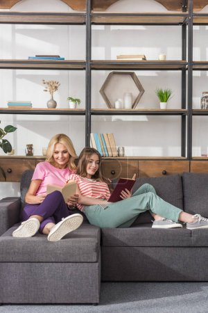 Photo pour Smiling mother and daughter sitting on sofa in living room and reading books - image libre de droit