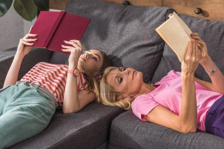 Photo pour Séduisante, femme mûre avec jolie, jeune fille couchée sur le canapé et la lecture de livres - image libre de droit
