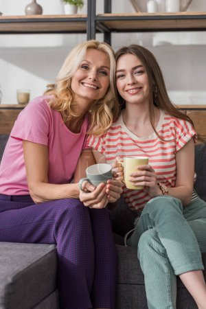 Photo for Happy mother and daughter looking at camera while sitting on sofa and holding tea cups - Royalty Free Image