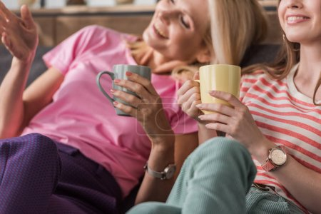 Photo for Selective focus of cheerful woman pointing with hand while sitting near daughter with tea cups - Royalty Free Image