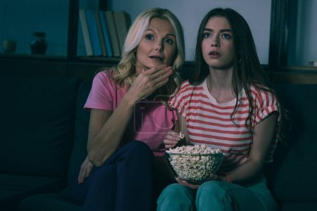 Photo for Focused mother and daughter watching tv and eating popcorn - Royalty Free Image