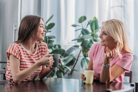 cheerful daughter and mother sitting at kitchen table, talking and drinking tea