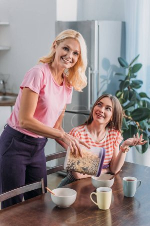 Photo for Smiling mature woman looking at camera and adding flakes in bowl while cheerful daughter sitting at kitchen table - Royalty Free Image
