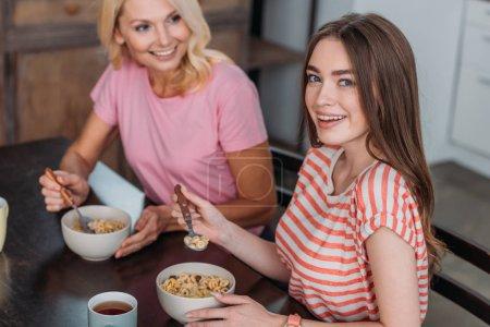 Photo pour Foyer sélectif de fille souriant à la caméra tout en prenant le petit déjeuner avec la mère - image libre de droit