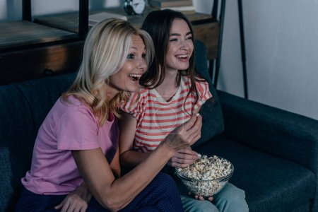 Photo for Exticed mother and daughter watching tv and eating popcorn - Royalty Free Image