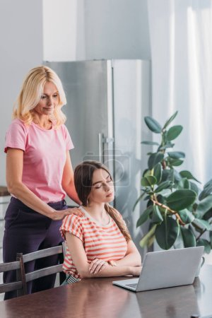 Photo for Beautiful mature woman touching shoulders of young daughter sitting near laptop in kitchen - Royalty Free Image