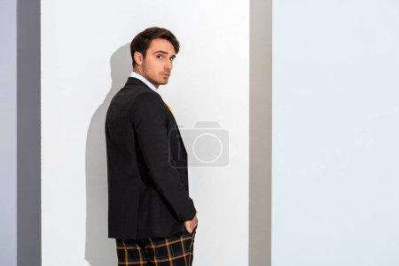Photo pour Bel homme en pantalon à carreaux debout sur blanc et gris - image libre de droit