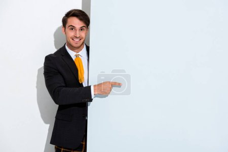 happy man in formal wear pointing with finger on white