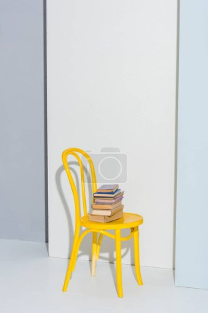 Photo for Yellow chair with books on white and grey - Royalty Free Image